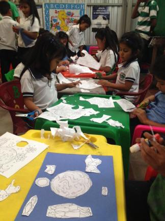 Some of the children from the youngest class working on a craft about when God created the earth.